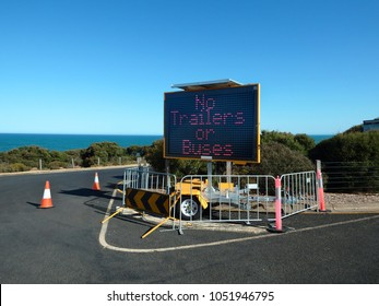 """A three row fixed character matrix LED sign warns """"No trailers - or buses """" placed on a barricade in a beach car park"""