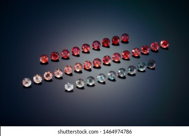 Three rows of round faceted sunstone show the range of color this gem material can come in. Shown on a black reflective background.