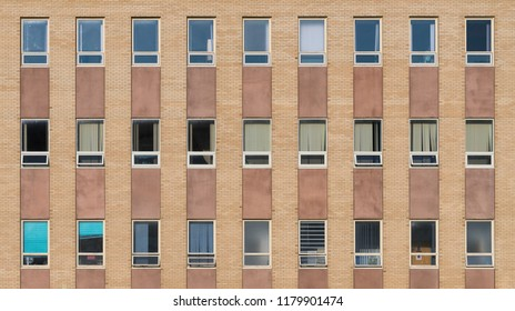 Three rows of windows against solid brick wall forms abstract background pattern