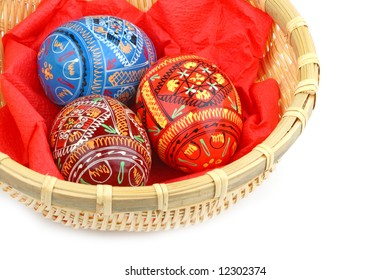 three russian tradition easter eggs in yellow basket close up over white