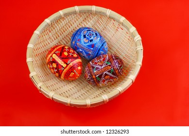 three Russian tradition easter eggs side be side in yellow basket over red