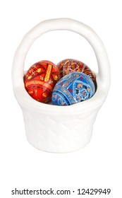 three russian tradition easter eggs in white porcelain basket over whit