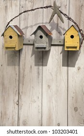Three rustic birdhouses hanging on a wooden fence.
