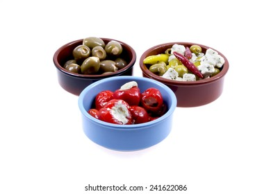 Three rustic bowls filled with antipasti on light background