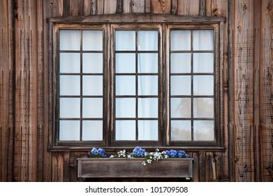 Three rustic windows with a window flower box
