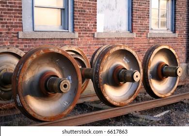 three rusty train axles beside three windows of a brick building