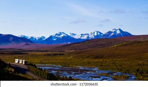 Three RVs overlook the Savage River valley and the Denali mountain range in Denali National Park in Alaska