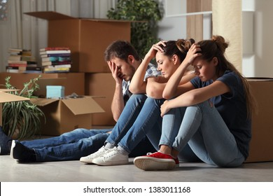 Three sad evicted roommates moving home complaining sitting on the floor