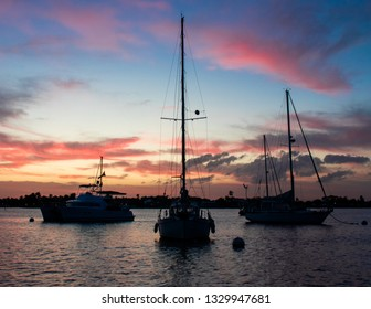 Three sailboats on the ocean at sunset. Silhouette in front of pink and blue sunrise in Stuart Florida on a spring day.