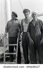 Three sailors posing together on ship deck