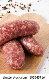 Three sausages on the chopping board  on  white backgroud, and pepper