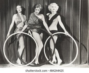 Three scantily clad women holding large rings