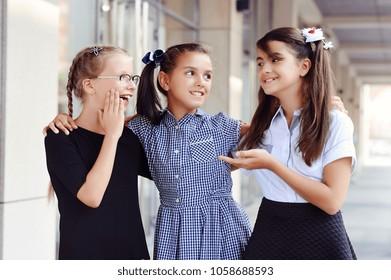 Three schoolgirls discussing during the school break