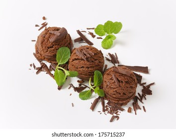 three scoops of chocolate ice cream with chocolate flakes and mint
