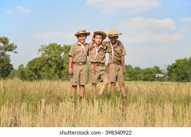 Three scouts stand neck of the field in the camp.