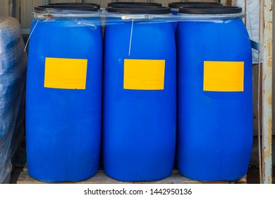 Three scratched blue barrels packed with orange labels on wooden pallets