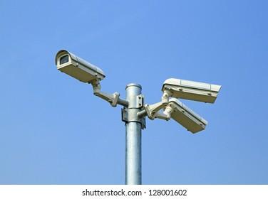 Three security cameras against blue sky