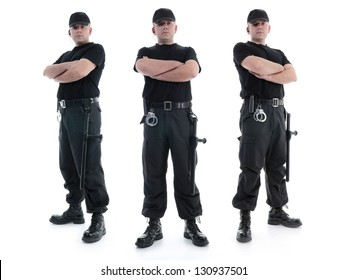 Three security men wearing black uniform equipped with police clubs and handcuffs standing confidently with arms crossed from left to right, shot on white