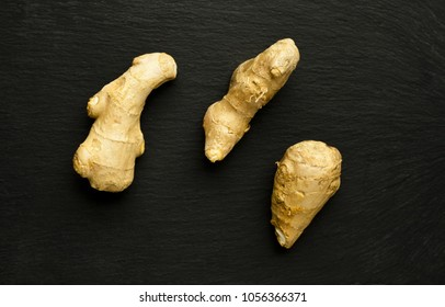 Three segments of organic ginger on black, slate surface