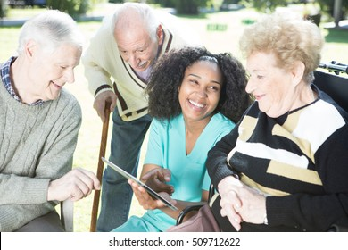 Three senior citizens in hospital garden learning to use tablet with nurse help.