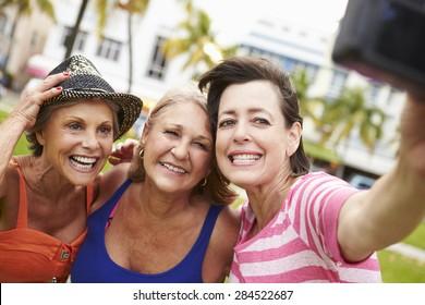 Three Senior Female Friends Taking Selfie In Park