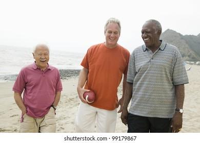 Three senior men walking on beach