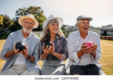 Three senior persons sitting in a park holding boules in their hands. Cheerful senior men and a woman having fun sitting outdoors enjoying the game of boules.