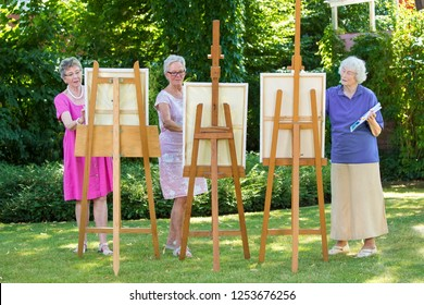 Three senior women painting on canvas in garden during sunny day.