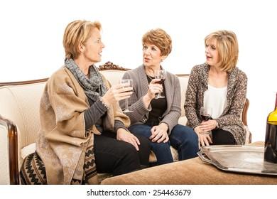 Three senior women sitting on a couch drinking wine