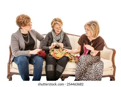 Three senior women sitting on a couch talking and knitting