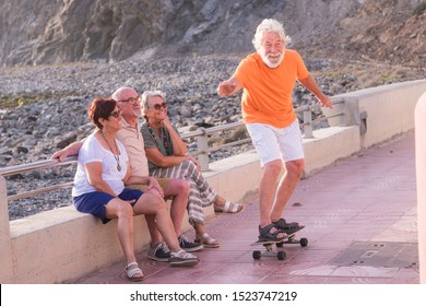 three seniors looking sitting on a bench at the beach looking at mature man trying to riding a skateboard for his first time - having fun and laughing together