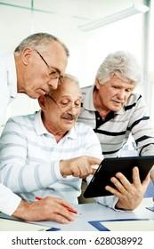 three seniors looking in tablet pc
