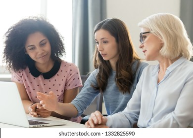 Three serious diverse young and old businesswomen working together focused looking at computer in office, female multi-ethnic business team employees discuss online project collaborating using laptop