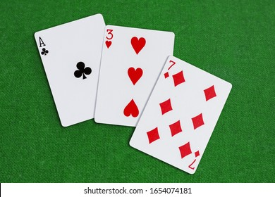 Three, Seven, Ace combination of playing cards laid out on the table covered with green baize