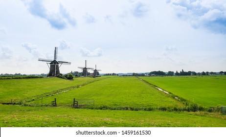 Three seventeenth century windmills in a farm field in Leidschendam in the Netherlands