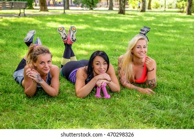 Three sexy athletic females lying on green lawn in a park.