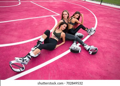 Three sexy girl sit on a pink playing field in kangoo jumping shoes. Kangoo sport and fitness in youth life.