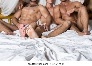 Three sexy guys are resting in bed. Love and relationships.