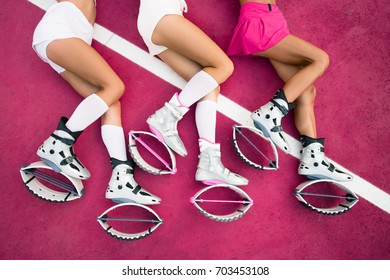 Three sexy legs of girls laying on the pink background and sexy exercises of legs in kangoo jumps shoes. Kangoo fitness outside. Girls wearing in sexy sport wear.