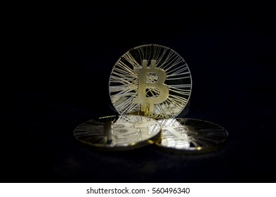 Three shiny bitcoin coins on black background
