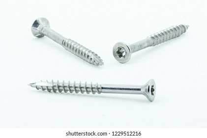 Three shiny stainless steel wood screws on white background