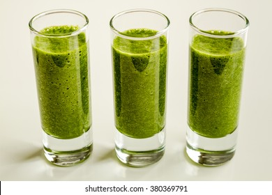 Three shot glasses filled with fresh spinach and kale detox health smoothie in a line