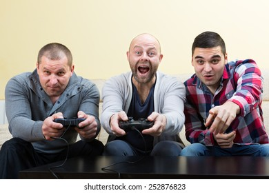Three shouting males playing video games at house party