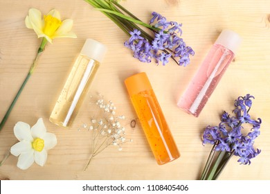 Three shower gels and beautiful flowers on a wooden background. Top view.