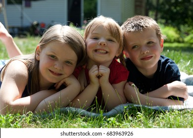three siblings outside in grass
