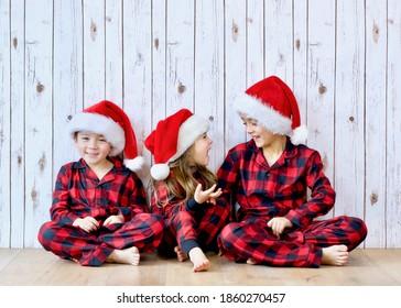 Three siblings wearing buffalo plaid pajamas and Santa hats sitting down and enjoying the winter holiday and Christmas vibe.