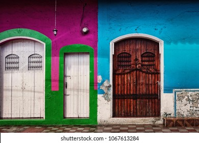 Three side-by-side colorful painted doorways with flaking paint and worn finish in the Colonial city of Leon in northern Nicaragua