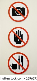 three signs forbidding photos, touching and food and drink