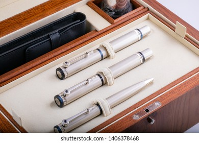 Three silver ballpoint pens in a gift set along with a holster, in a wooden, lacquered box.