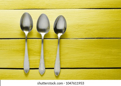Three silver spoons on a yellow wooden table. Top view. Copy space.